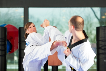 black belt: People in a gym in martial arts training exercising Taekwondo, both have a black belt