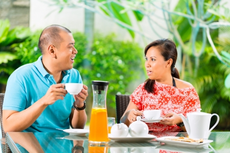 Asian couple having coffee on the porch in front of their home, in a tropical garden photo