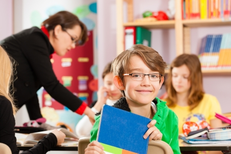 teaching material: Education - Pupils and teacher learning at elementary or primary school in the classroom Stock Photo