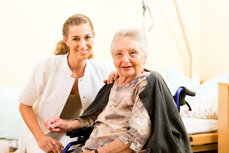 oldage: Young nurse and female senior in nursing home, the old lady sitting in a wheel chair Stock Photo