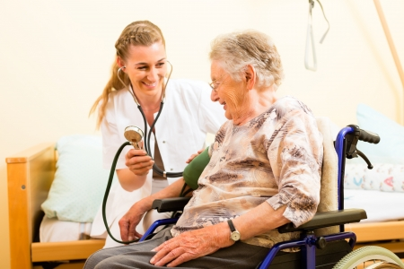 old people in care: Young nurse and female senior in nursing home, the blood pressure is going to be measured Stock Photo