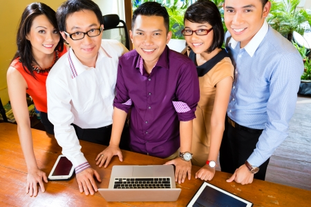 Asian Creative business agency - team meeting in an office with laptop Stock Photo - 23964701