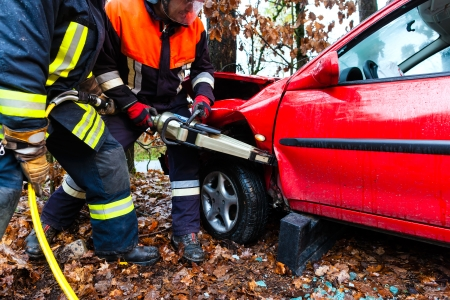 Accident - Fire brigade rescues accident Victim of a car using a hydraulic rescue tool Stock Photo - 23964831