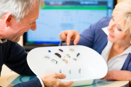 Hearing: Older man and woman or pensioners with a hearing problem make a hearing test and may need a hearing aid