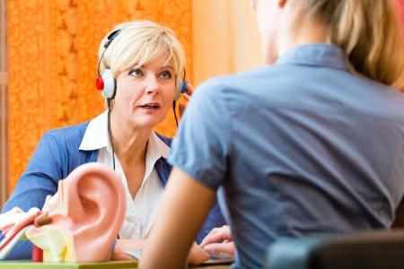 personas escuchando: Mujer mayor o pensionista femenina con un problema de audici�n hacen una prueba de audici�n y pueden necesitar un aparato auditivo, en el primer plano es un modelo de un o�do humano