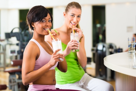protein: Young People - women in the gym drinking a isotonic drink or protein shake  Stock Photo