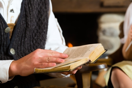 trachten: Young man in a traditional mountain hut with fireplace reading the bible