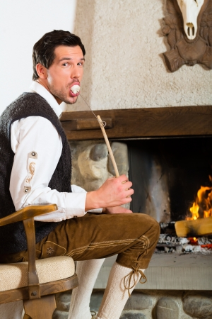 trachten: Young man in a traditional mountain hut with fireplace eating marshmallow