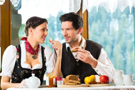 trachten: Couple in a traditional mountain hut having a hearty breakfast