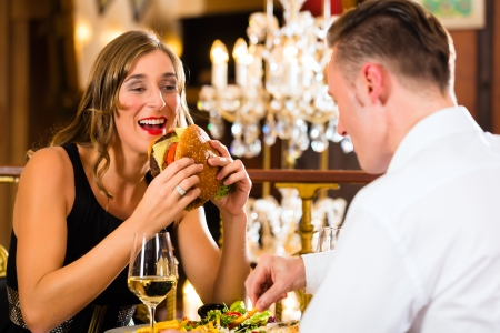 burger and fries: Couple - man and woman - in a fine dining restaurant they eat fast food, burger and fries - a large chandelier