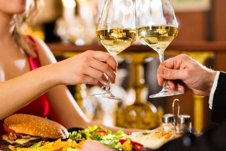 clinking: feliz pareja tener una cita rom�ntica en un restaurante elegante que beben copas de vino y tintineo, gritos - una gran l�mpara de ara�a est� en segundo plano Foto de archivo