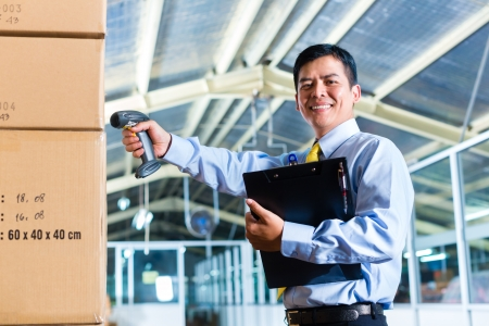 Young Indonesian man in a suit with a bar code scanner in a Asian warehouse photo