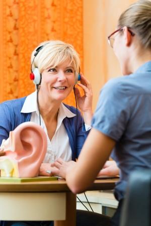 personas escuchando: Mujer de edad avanzada o jubilada con un problema de audici�n hacen una prueba de audici�n y pueden necesitar un aud�fono, en el primer plano es un modelo de un o�do humano Foto de archivo