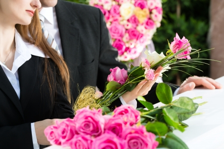 mortician: Mourning man and woman on funeral with pink rose standing at casket or coffin