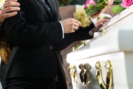 Deuil homme et femme sur funéraire avec rose rose debout au cercueil ou le cercueil Banque d'images - 23964965