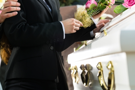 funeral parlor: Mourning man and woman on funeral with pink rose standing at casket or coffin