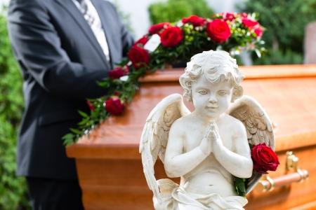 Mourning hombre en el funeral con una rosa roja que se coloca en el ataúd o féretro Foto de archivo