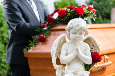 funeral parlor: Mourning man on funeral with red rose standing at casket or coffin