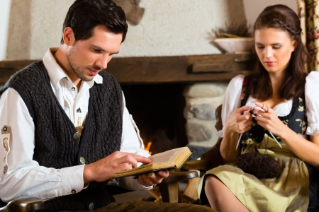 hunter's cabin: Couple in a traditional mountain hut with fireplace knitting and reading the bible