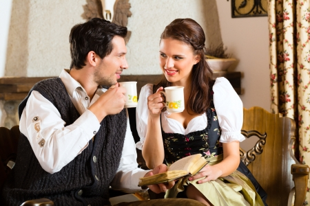 trachten: Couple in a traditional mountain hut with fireplace drinking coffee or tea