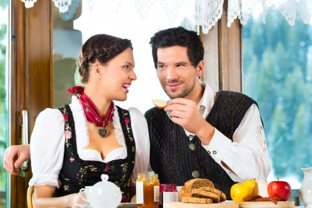 hunter's cabin: Couple in a traditional mountain hut having a hearty breakfast