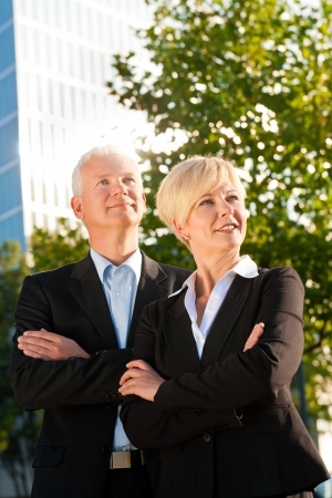 senior business: Business people - mature or senior - standing in a park outdoors in front of a office building Stock Photo