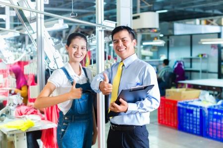 Costureira indonésia é nova designada em uma fábrica têxtil, o capataz dá seu treinamento para o novo emprego Foto de archivo - 24098670
