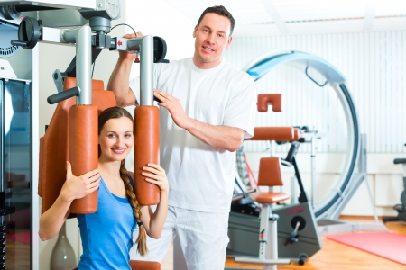 Patient at the physiotherapy making physical exercises with her therapist Stock Photo