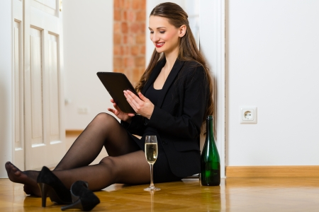 Online Dating - Young businesswoman sitting at home on the floor while using a tablet computer for online dating