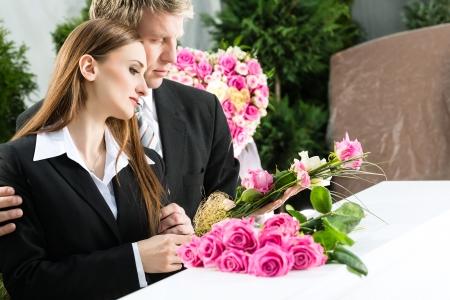 luto: Duelo hombre y la mujer en el funeral con rosa de pie en ataúd o féretro