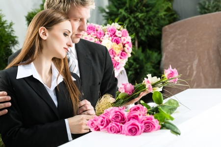 kin: Mourning man and woman on funeral with pink rose standing at casket or coffin