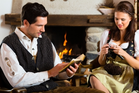 Couple in a traditional mountain hut with fireplace knitting and reading the bible Stock Photo - 24098698