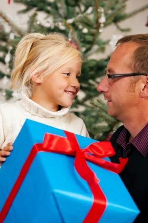 dar un regalo: Chica joven que recibe un regalo de su padre para la Navidad, escena familiar Foto de archivo