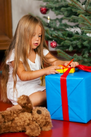 christmas morning: Cute Child with teddy bear toy finding her Christmas present in the morning still in her sleepwear and unwrapping it
