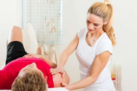 Patient at the physiotherapy doing physical therapy exercises with his therapist photo