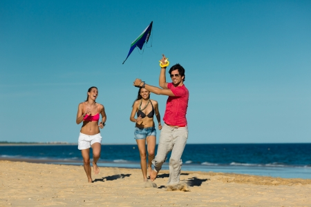 flying kite: Group of young people playing with a kite on beach in sand outdoors in summer Stock Photo
