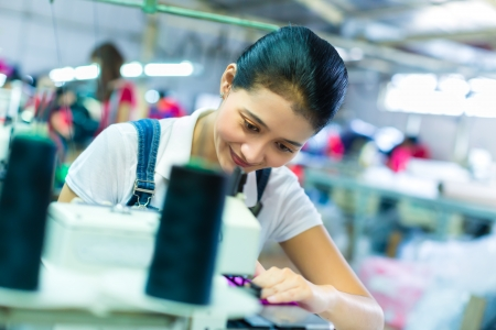 precisely: Asian Seamstress or worker in a Indonesian factory sewing with a industrial sewing machine, she is very accurate Stock Photo