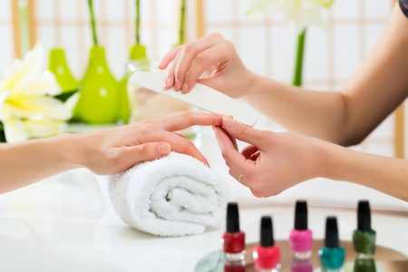 manicure: Woman in a nail salon receiving a manicure by a beautician Stock Photo