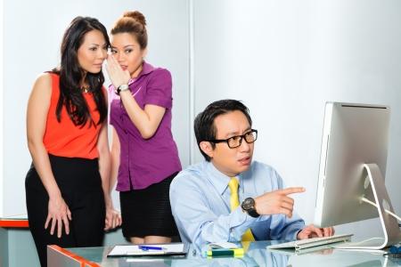 Asiatische Frauen oder Mitarbeiter s Tratsch oder Flüstern über Kollegen oder Mann, ihm Mobbing im Büro Standard-Bild