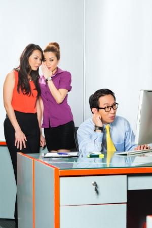 Asiatische Frauen oder Mitarbeiter s Tratsch oder Flüstern über Kollegen oder Mann, ihm Mobbing im Büro
