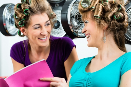 women at the hairdresser reading a magazine or a rag and chit-chat, while your hair drying under a hairdryer photo