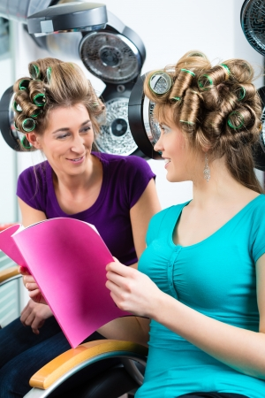 chitchat: women at the hairdresser reading a magazine or a rag and chit-chat, while your hair drying under a hairdryer