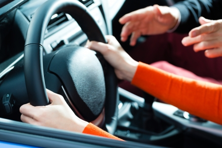 instructors: Driving School - Young woman steer a car with the steering wheel, maybe she has a driving test perhaps she exercises the parking
