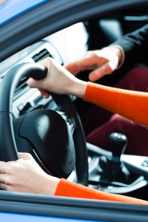 instructor: Driving School - Young woman steer a car with the steering wheel, maybe she has a driving test perhaps she exercises the parking