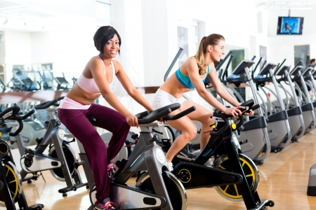Young People - women Spinning in the gym on fitness bicycles photo