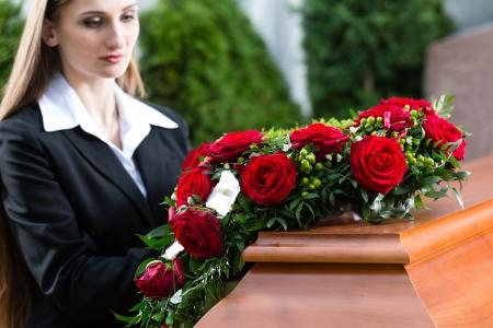 luto: Mujer de luto en el funeral con una rosa roja de pie en ataúd o féretro Foto de archivo