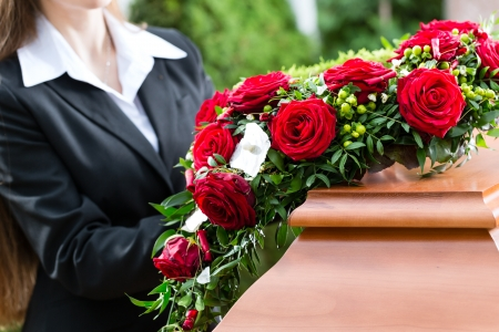 mortician: Mourning woman on funeral with red rose standing at casket or coffin