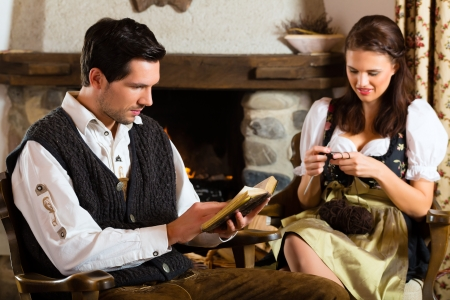 trachten: Couple in a traditional mountain hut with fireplace knitting and reading the bible
