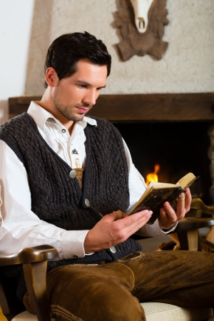 Young man in a traditional mountain hut with fireplace reading the bible Stock Photo - 24099065