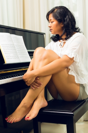 Asian woman sitting at the piano in her living room Stock Photo - 24283614